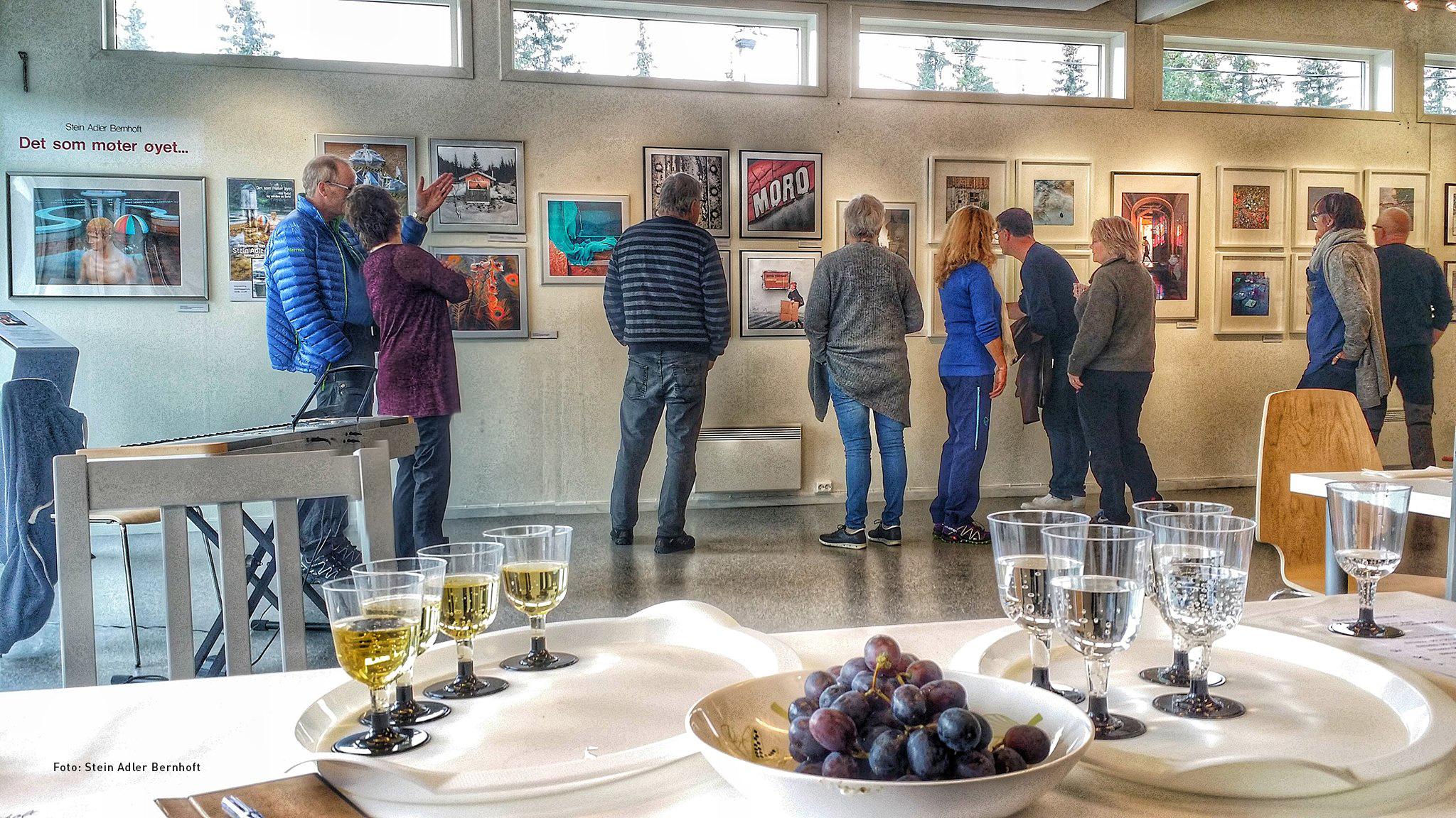 Utstilling av bilder med mange besøkende.